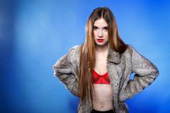 sexy woman in fur coat and red bra - stock photo