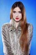 portrait of young woman in fur blue background - stock photo