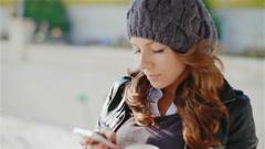 Happy girl enjoys a smartphone Stock Footage
