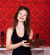 beautiful woman with wooden box smiling in red vintage interior - stock photo