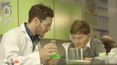 School teacher and schoolboy working in laboratory Stock Footage