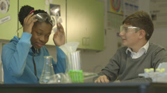 Teacher with student in science class Stock Footage