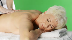 Senior woman heaving massage, over green screen background Stock Footage