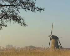 Kinderdijk windmill in winter landscape - cyclists passing. Stock Footage