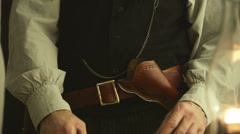 Stock Video Footage of old west cowboy loading a pistol in his cross draw holster