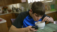 teenage boy uses smart phone while eating cereal - stock footage