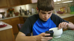 Teenage boy eating listens to music on smart phone Stock Footage