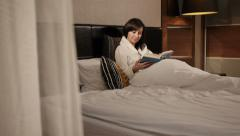 Girl reading a book at home Stock Footage