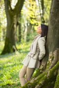 Stock Photo of Woman leaning on a tree