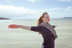 Attractive woman opening her arms in front of the ocean Stock Photos