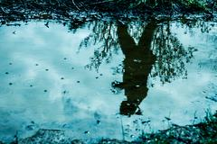 Reflection of a woman in a puddle Stock Photos