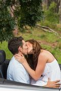 Happy couple kissing on the backseat Stock Photos