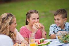 Young girl eating burger while mother and brother smiling at her Stock Photos