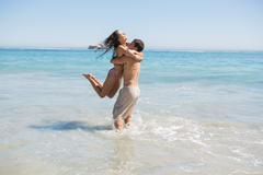 Handsome man holding his girlfriend in the sea Stock Photos