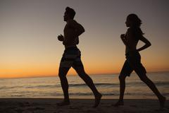 Sporty couple running together on the beach Stock Photos