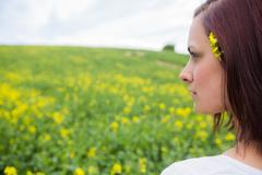 Brunette looking at field of yellow flowers - stock photo