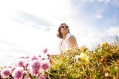 Woman sitting in field of wild flowers Stock Photos