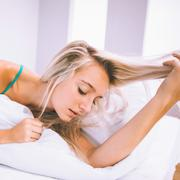 Gorgeous calm blonde lying on bed holding her hair Stock Photos