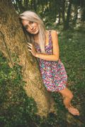 Content gorgeous blonde leaning against tree looking at camera - stock photo