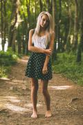 Stock Photo of Serious gorgeous blonde standing on forest track