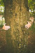 Stock Photo of Picture of young woman embracing a trunk