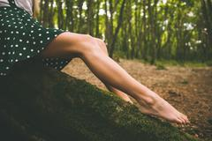 Legs of a woman wearing a dotted skirt sitting on tree - stock photo
