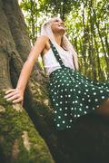 Low angle picture of smiling gorgeous blonde leaning against tree - stock photo