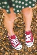 Picture of female feet wearing red trainers Stock Photos