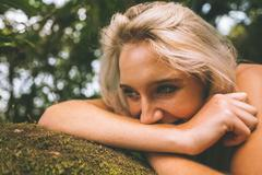 Stock Photo of Happy gorgeous blonde lying on trunk