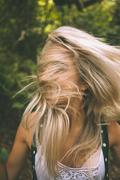 Happy blonde having her face covered by hair - stock photo