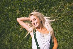 Smiling gorgeous blonde lying on lawn Stock Photos