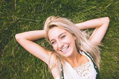 Happy gorgeous blonde lying on lawn Stock Photos