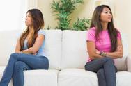 Stock Photo of Two annoyed sisters sitting on a sofa