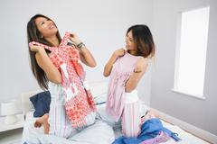 Stock Photo of Two happy sisters trying on some clothes