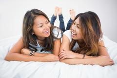 Pretty brunette sisters lying on a bed Stock Photos