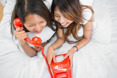 Two sisters making a call on an old fashioned dial phone - stock photo