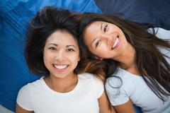 Two young women lying on a bed Stock Photos