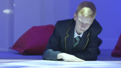 Schoolboy lying down Stock Footage