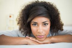 Pretty unsmiling brunette lying on bed resting head on hand Stock Photos