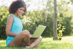 Gorgeous smiling brunette sitting cross legged on grass holding laptop - stock photo