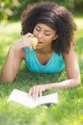 Gorgeous content brunette reading book eating apple Stock Photos