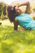 Gorgeous thoughtful brunette lying on grass touching head Stock Photos