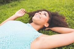 Stock Photo of Gorgeous cheerful brunette lying on grass holding lock of hair