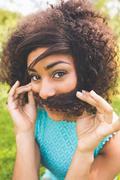 Gorgeous happy brunette pretending she has a mustache - stock photo