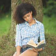 Gorgeous serious brunette leaning against tree reading - stock photo
