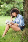 Gorgeous unsmiling brunette reading under tree - stock photo