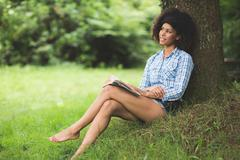 Gorgeous content brunette leaning against tree reading - stock photo