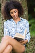 Stock Photo of Gorgeous peaceful brunette reading under tree