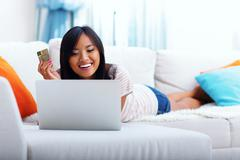 happy asian woman shopping on-line while lying on the sofa - stock photo