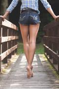Rear view of lower body of model walking on bridge Stock Photos